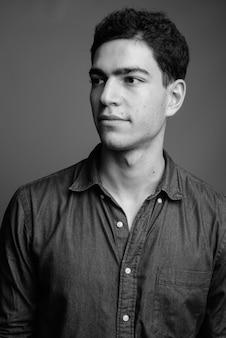 Giovane uomo d'affari persiano bello contro il muro grigio in bianco e nero