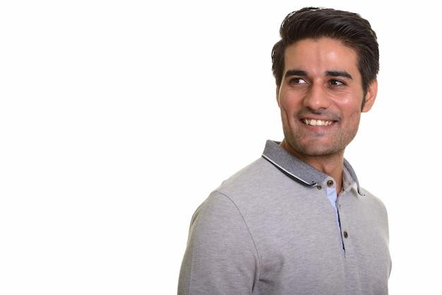 Giovane uomo persiano bello contro il muro bianco