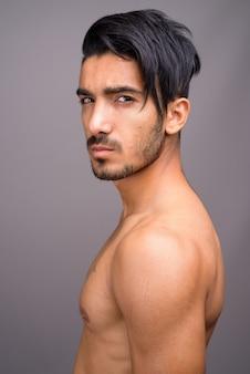 Giovane uomo persiano bello a torso nudo su sfondo grigio