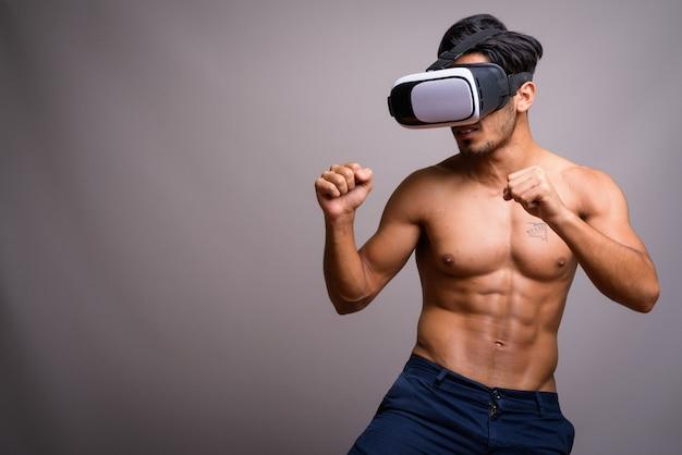 Giovane uomo persiano bello utilizzando le cuffie da realtà virtuale senza camicia