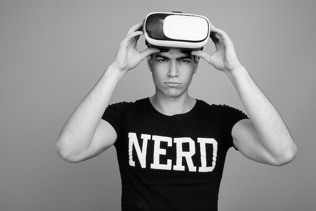 Giovane e bello nerd persiano con gli occhiali contro il muro grigio in bianco e nero