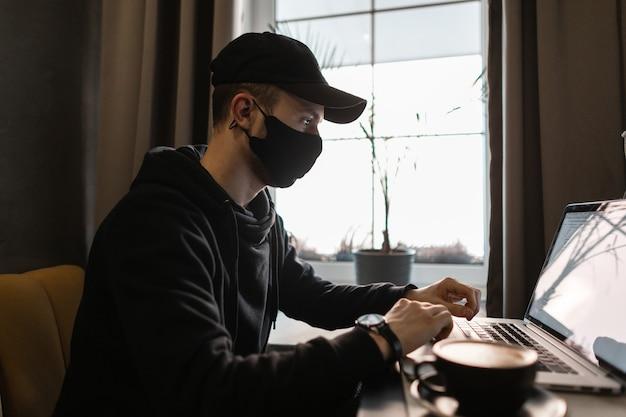 Il giovane bel professionista in abiti neri alla moda con una felpa con cappuccio, un berretto nero e una maschera protettiva lavora su un laptop e beve caffè in una caffetteria