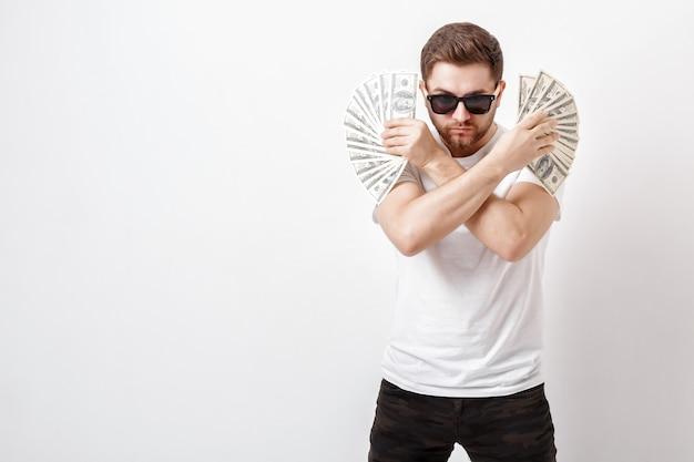 Giovane uomo serio bello con la barba in una camicia bianca che tiene un sacco di banconote da cento dollari. soldi