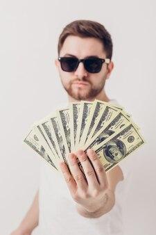 Giovane uomo sorridente bello con la barba in una camicia bianca che tiene un sacco di banconote da cento dollari. concentrarsi sui soldi. luce soffusa