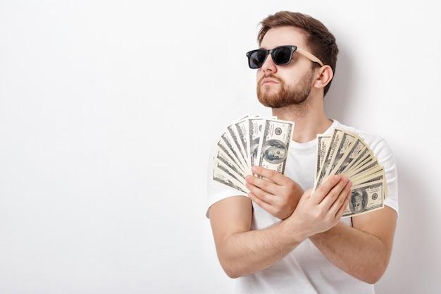 Giovane uomo sorridente bello con la barba in una camicia bianca che tiene un sacco di banconote da cento dollari. concentrati sui soldi