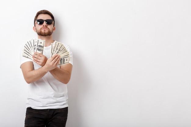 Giovane uomo sorridente bello con la barba in una camicia bianca che tiene un sacco di banconote da cento dollari. soldi