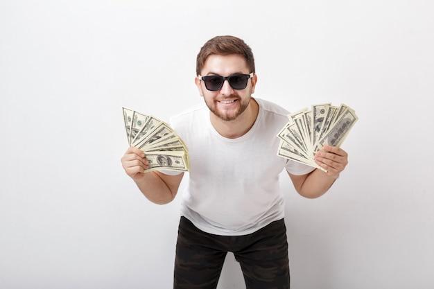 Giovane uomo sorridente bello con la barba in una camicia bianca e occhiali da sole con in mano un sacco di banconote da cento dollari e guardando la telecamera. soldi