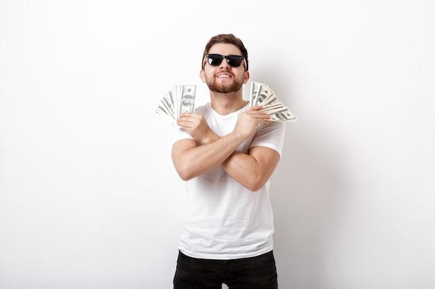 Giovane bell'uomo sorridente con la barba in camicia bianca e occhiali da sole con in mano un sacco di banconote da cento dollari. soldi