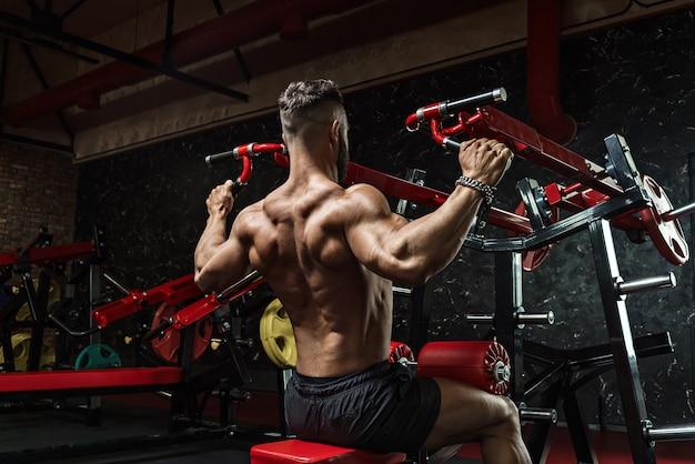 Sollevatore di pesi giovane culturista sportivo bello con un corpo ideale, dopo l'allenatore pone davanti alla telecamera, muscoli addominali, tricipiti bicipiti. in abbigliamento sportivo.