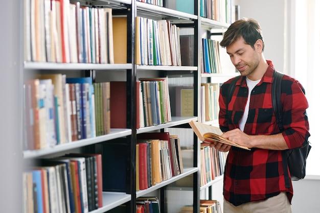 Giovane allievo bello che legge uno dei libri nella biblioteca dell'università mentre sceglie la letteratura educativa