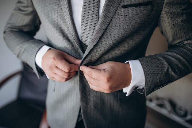 Il giovane uomo alla moda bello si è vestito in giacca abbottonatura moderna dei vestiti convenzionali. primo piano delle mani del ragazzo in giacca grigia, camicia viola. persona pronta per la celebrazione del matrimonio o laurea.
