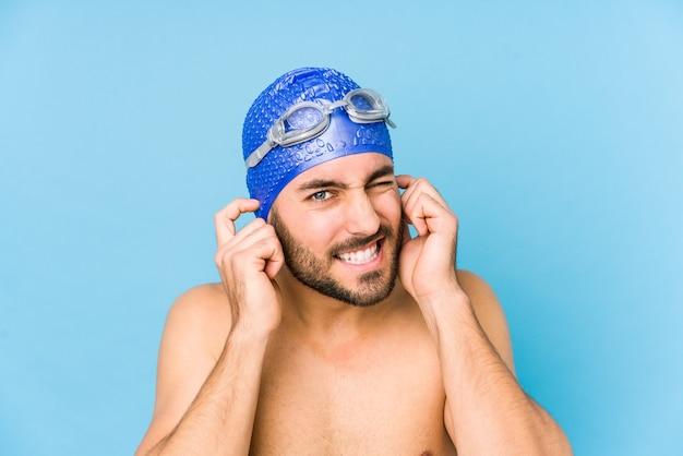 Giovane uomo bello nuotatore isolato che copre le orecchie con le mani