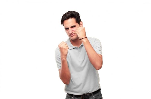 Giovane uomo bello abbronzato con una posa arrabbiata, aggressiva e minacciosa, pronta per la lotta, mostrando