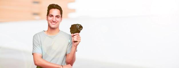 Giovane uomo abbronzato bello con una macchina da presa del cinema dell'annata