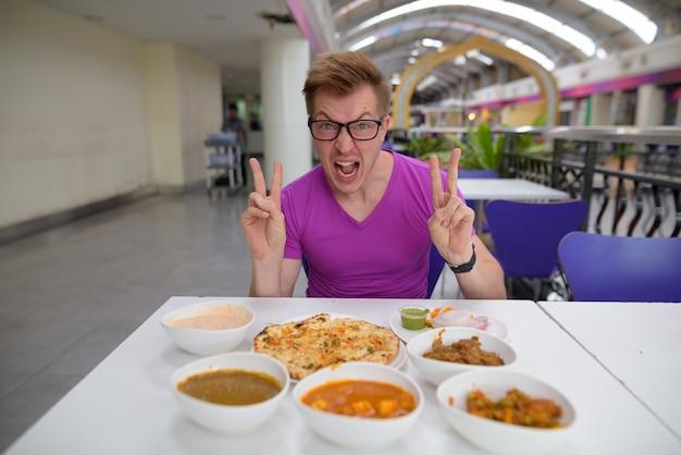 Bel giovane turista che gode della cucina indiana
