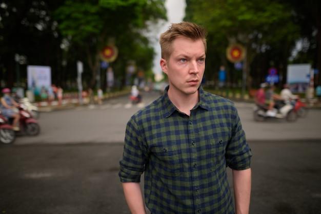 Giovane uomo turistico bello che esplora la città di ho chi minh nel vietnam