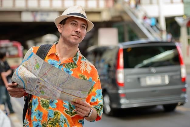 Giovane turista bello con zaino pensando durante la lettura della mappa nelle strade della città