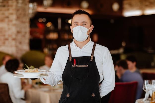 Giovane cameriere bello in grembiule nero e mascherina medica che tiene piatto con spaghetti su sfondo ristorante.