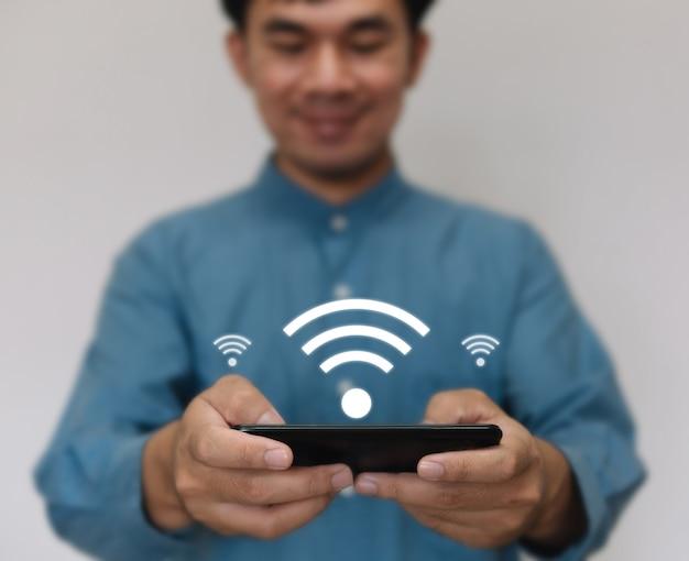 Il giovane bello che indossa una maglietta azzurra usa la tecnologia wi-fi per utilizzare la funzione di casa intelligente.