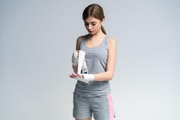 Giovane donna bella avvolgendo le mani con una fascia, preparandosi per l'allenamento di boxe