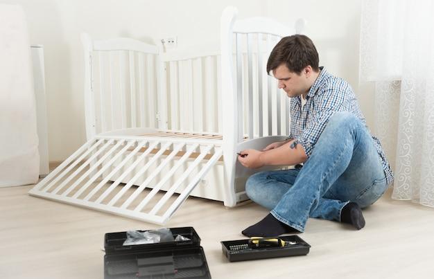 Giovane tuttofare che monta mobili in legno nella stanza dei bambini
