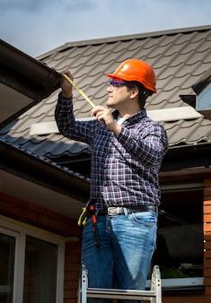 Giovane tuttofare in piedi su una scala alta e misura il tetto con nastro adesivo