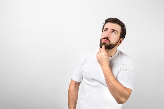 Il giovane e vecchio uomo è in piedi vicino al muro bianco e tiene la mano sinistra vicino al mento. sta pensando e guardando da qualche parte a parte. isolato sul muro bianco.