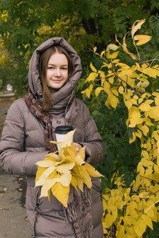 Giovane felicità bella ragazza con caffè e foglie gialle colori della stagione autunnale autunnale