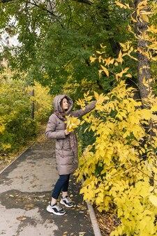 Giovane felicità bella ragazza con foglie gialle colori della stagione autunnale autunnale