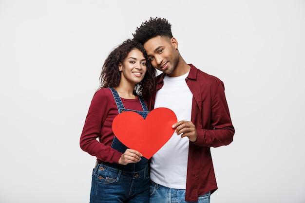 Giovane coppia afroamericana felice nell'amore che tiene il cuore di carta rosso.
