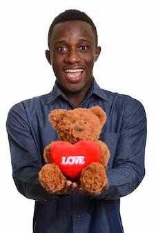 Giovane uomo africano felice che sorride e che dà orsacchiotto con il cuore