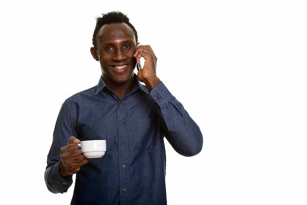 Giovane uomo africano felice che sorride mentre parlando sul telefono cellulare