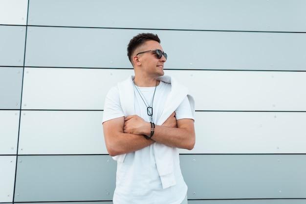 Giovane uomo americano felice in occhiali da sole in jeans blu alla moda in una maglietta bianca alla moda è in posa in città vicino a un moderno muro a strisce. ragazzo allegro con acconciatura all'aperto in una giornata estiva.