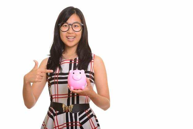 Giovane donna di affari asiatica felice che tiene banca piggy e dito puntato