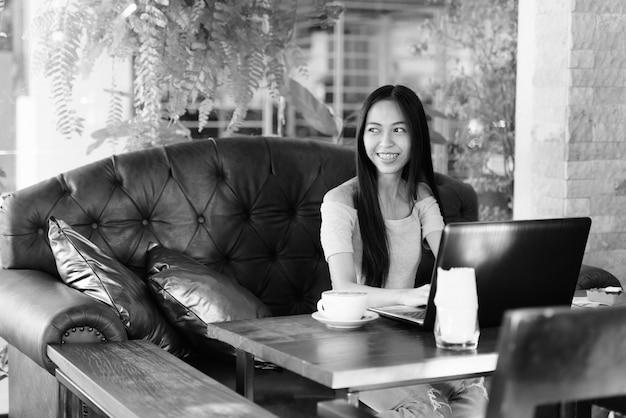 Giovane ragazza asiatica felice che sorride mentre pensa alla caffetteria all'aperto con laptop e cappuccino su un tavolo di legno