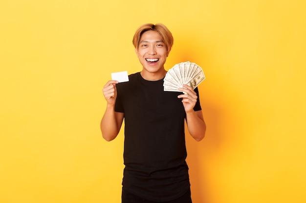 Giovane uomo asiatico felice con capelli biondi