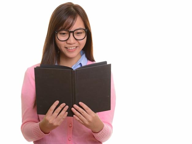Giovane adolescente asiatico felice sorridente e libro di lettura