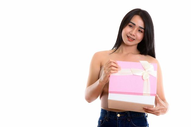 Giovane donna transgender asiatica felice che sorride mentre apre il contenitore di regalo