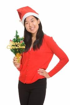 Giovane donna asiatica felice che tiene l'albero di natale allegro pronto per natale isolato