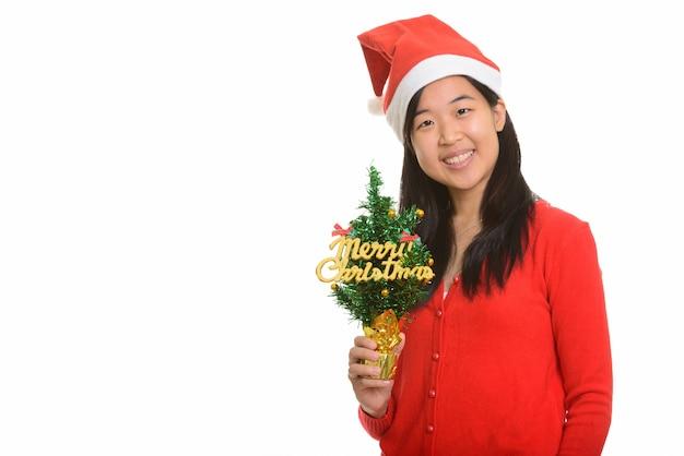 Giovane donna asiatica felice che tiene l'albero di natale allegro pronto per il natale