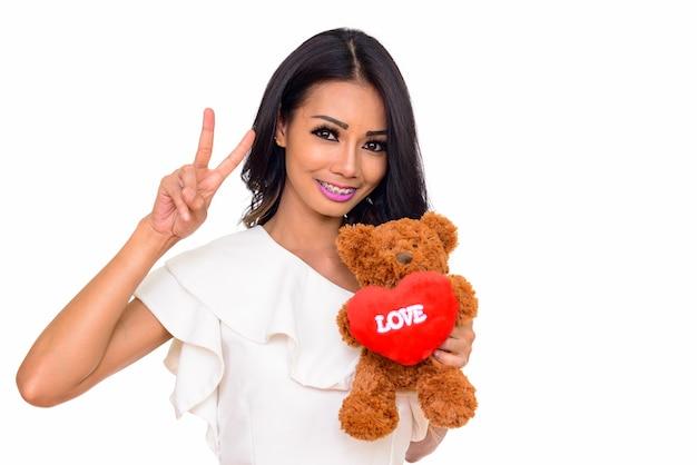Giovane donna asiatica felice azienda orsacchiotto con cuore e amore segno isolato su bianco