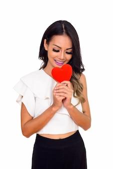 Giovane donna asiatica felice in amore tenendo il cuore isolato su bianco