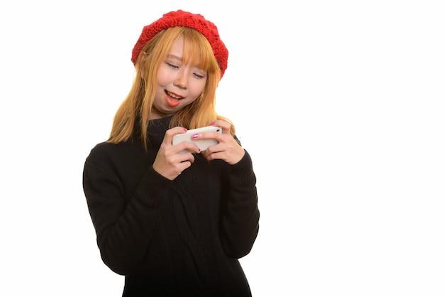 Giovane donna asiatica felice sorridente e utilizzando il telefono cellulare