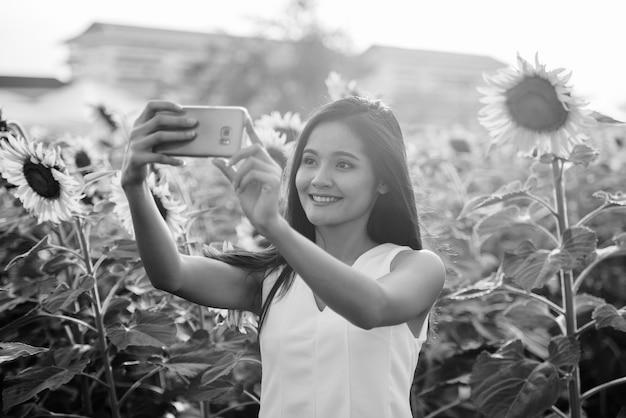 Giovane donna asiatica felice che sorride mentre scatta una foto selfie con il telefono cellulare nel campo dei girasoli in fiore