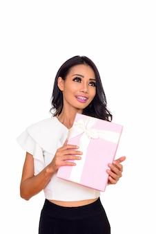 Giovane donna asiatica felice pensando tenendo confezione regalo isolata on white