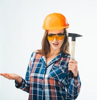 Giovane ragazza attraente felice nella costruzione di casco arancione e occhiali con martello. immagine completa dello studio isolata dall'artigiana emotiva.