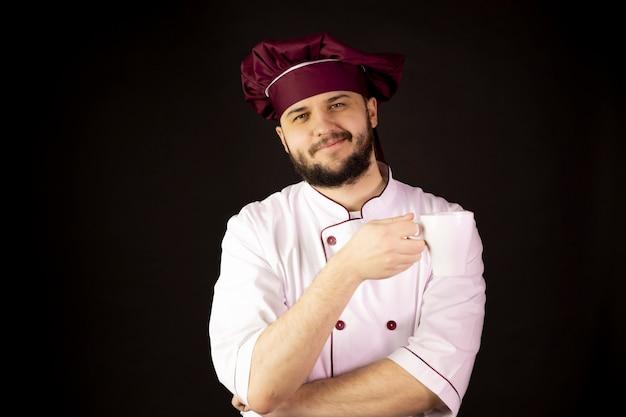 Il giovane chef barbuto felice in uniforme tiene la tazza di tè, caffè e sorriso