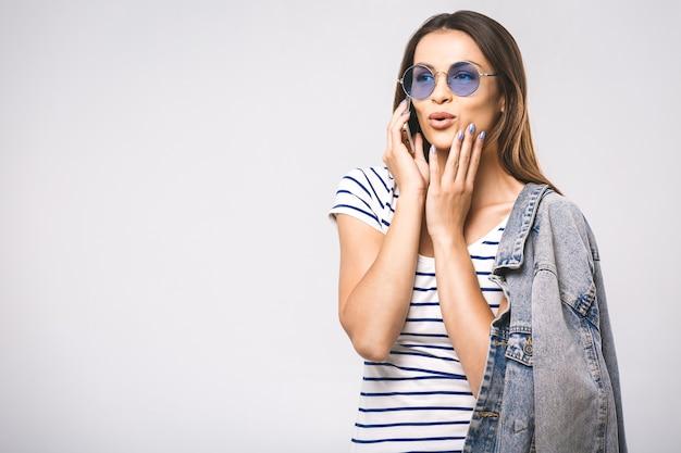Giovane bella donna felice di modo con gli occhiali da sole utilizzando il telefono