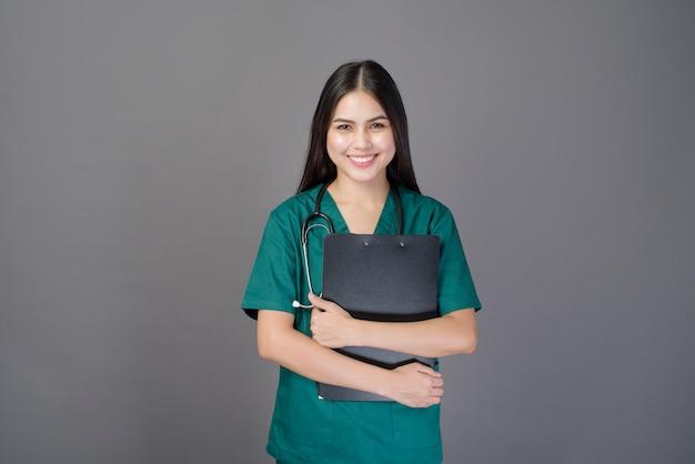 Il giovane bello medico felice della donna che indossa un verde sfrega sta tenendo i documenti
