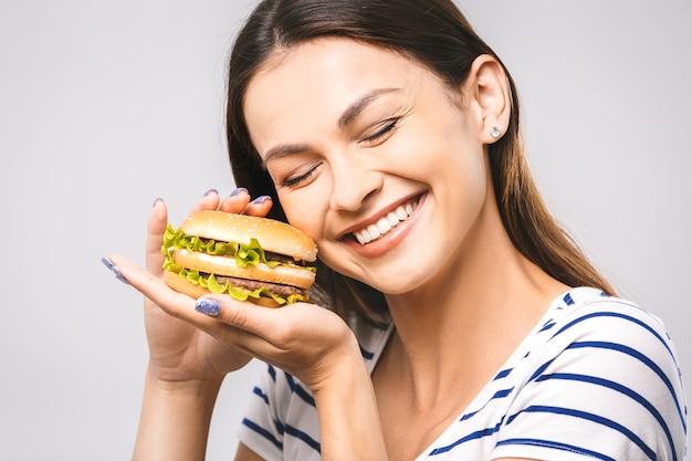 Giovane bella donna felice che mangia hamburger